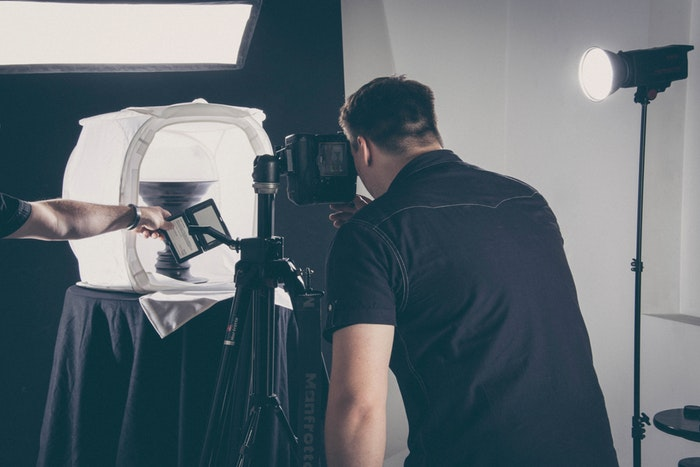 A professional photographer taking a product picture in a studio