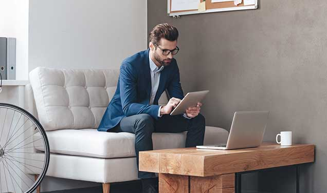 Businessman sitting on couch and using tablet