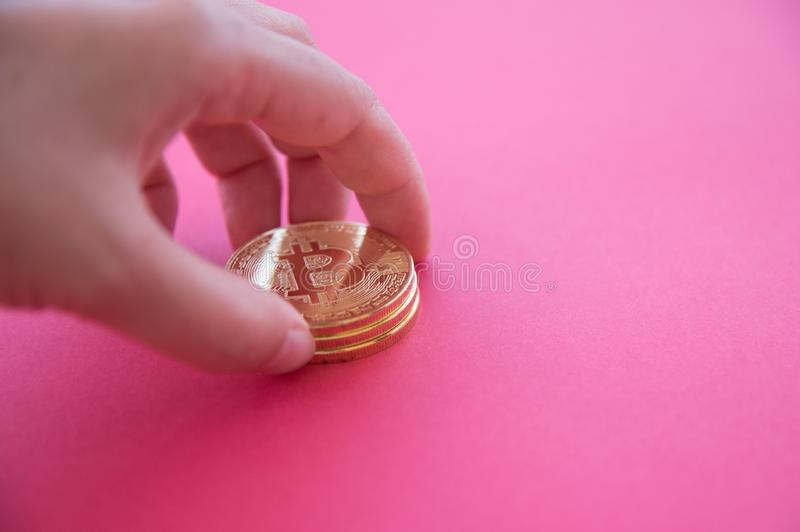 A hand collecting Bitcoins with red surface in the background. A hand collecting golden  Bitcoins with red surface in the background. With copy space stock photography