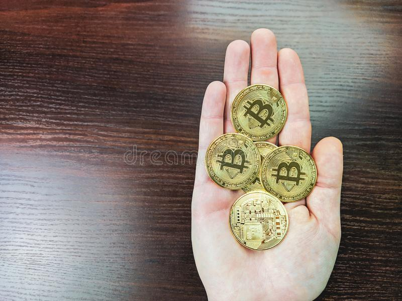 A hand palm full of golden bitcoins, collecting electronic cryptocurrency by mining and halving, using them for worldwide internet. Global exchange and stock images