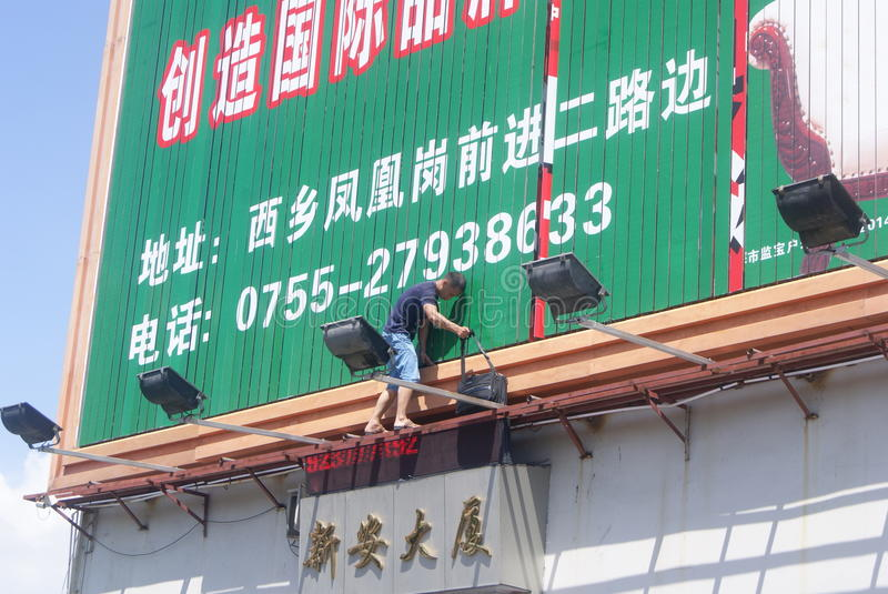 Shenzhen, China: installation of advertising signs. Shenzhen Baoan Xixiang, a worker is installed advertising signs royalty free stock photo