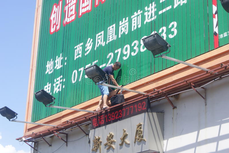 Shenzhen, China: installation of advertising signs. Shenzhen Baoan Xixiang, a worker is installed advertising signs stock images