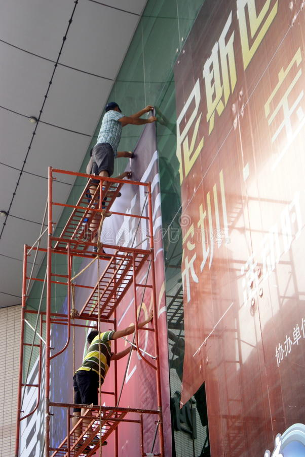 Shenzhen, China: installation of advertising signs. Shenzhen Baoan Xixiang, the workers install billboards at high altitude stock photos