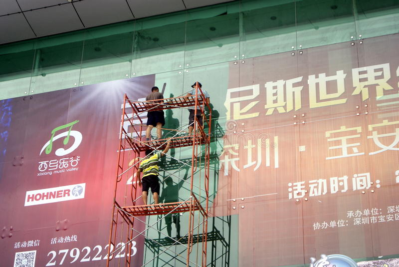 Shenzhen, China: installation of advertising signs. Shenzhen Baoan Xixiang, the workers install billboards at high altitude stock images